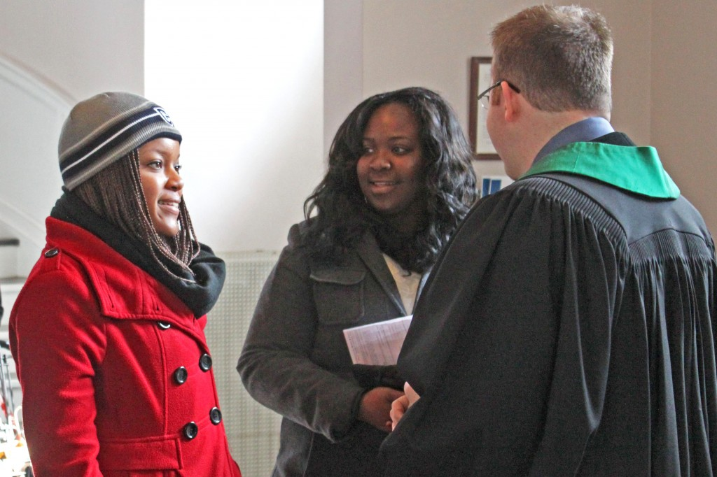 Pastor Matt greeting two UConn students after worship